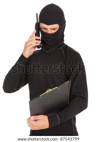 young male thief in balaclava with mobile phone and clipboard, white background - stock photo
