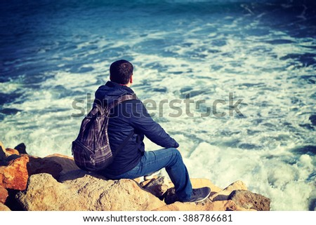 Young male traveler sitting on the rocks and enjoy the views of the sea and nature in Varna Bulgaria
