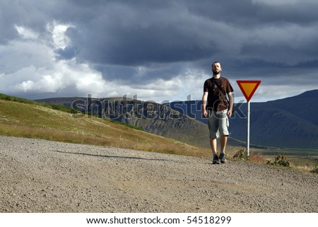 Young male traveller, photographer hitchhiking along the road in beautiful mountains of Iceland - stock photo