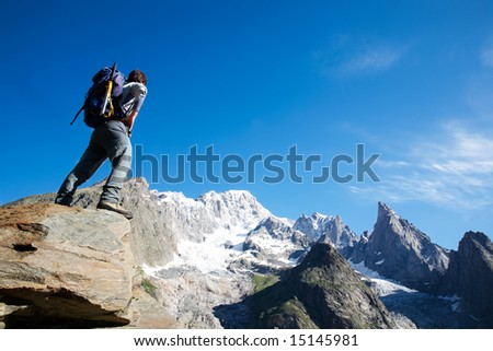 Young male trekker looking at Mont Blanc south face; Mont Blanc, italian side, Courmayeur, Italy. - stock photo