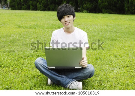 Young male university student sitting on the grass working on laptop at campus - stock photo