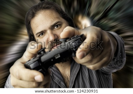 Young male using a video game controller with a smile. Isolated portrait on white with copyspace, eyes in focus with blurred controller in front, Stressful look on his face - stock photo