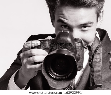 Young male using professional camera - stock photo