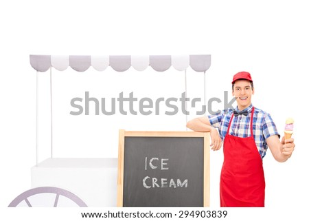 Young male vendor standing by an ice cream stand and holding an ice cream cone isolated on white background - stock photo