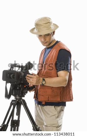 Young male videographer adjusting a videography camera on a tripod - stock photo