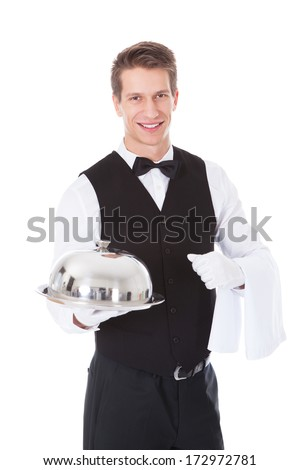 Young Male Waiter Holding Cloche Lid Cover Over White Background - stock photo
