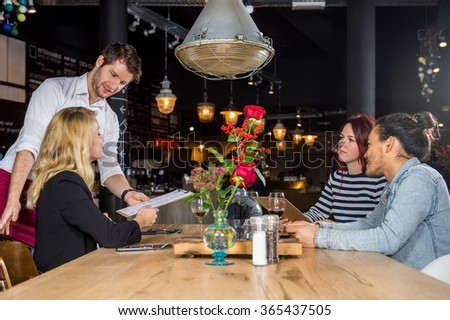 Young male waiter presenting menu to customers at table in bar - stock photo
