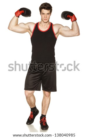 Young male wearing boxing gloves showing his muscles against white background - stock photo