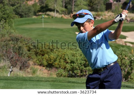 Young male with blue shirt about to hit a ball on a beautiful golf course with flag visible, focus on golfer - stock photo