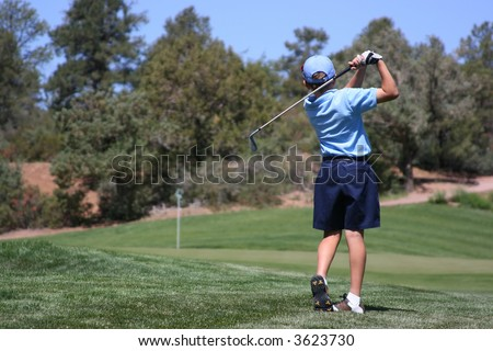 Young male with blue shirt hitting ball on green with flag visible, focus on golfer - stock photo