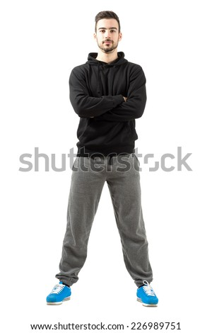 Young male with folded or crossed hands in the sportswear. Full body length isolated over white background. - stock photo