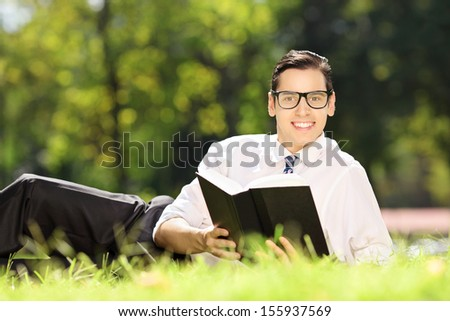 Young male with glasses lying on a green grass with book and looking at camera in park - stock photo