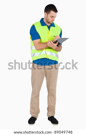 Young male with safety jacket taking notes against a white background - stock photo