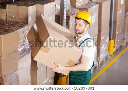 Young male worker is holding box in warehouse - stock photo