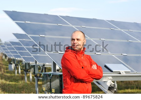 Young male worker with solar panels in background - stock photo