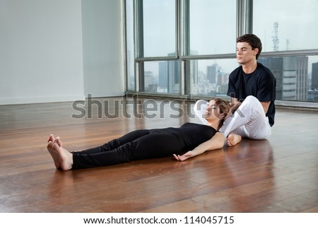 Young male yoga instructor helping female trainee with a pose at gym - stock photo