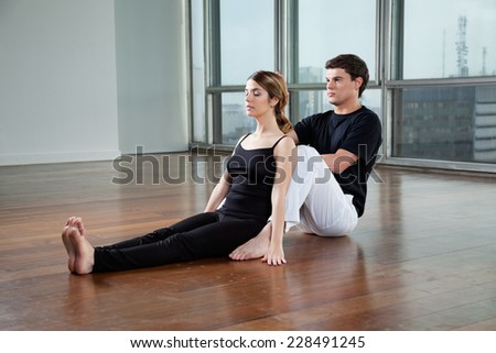 Young male yoga instructor helping woman with a pose at gym - stock photo