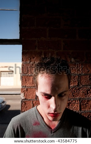 Young Male Zombie Standing in front of Brick Wall - stock photo