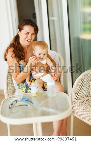 Young mama feeding baby on terrace - stock photo