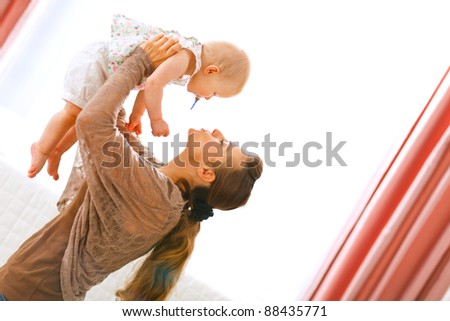 Young mama playing with baby by rising her up at home - stock photo