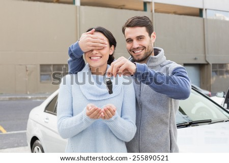 Young man about to surprise girlfriend with new car outside their car - stock photo