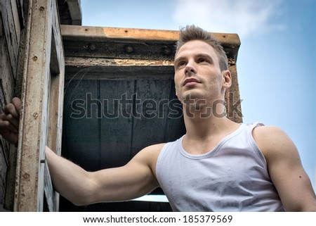 Young man against old rusty metal door and wood, photographed from below. - stock photo