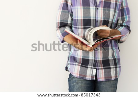 Young man against the wall reading a book - stock photo