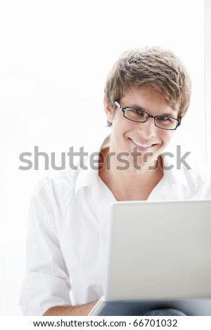 Young man against the window with a laptop - stock photo