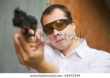young man aiming a black gun  against  the brick wall