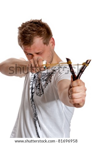 Young man aiming a slingshot poses in the studio on a white background