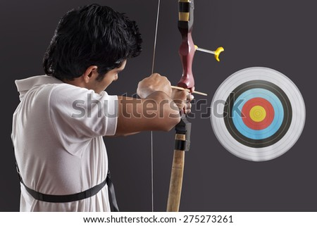 Young man aiming target with bow against black background - stock photo
