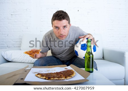 young man alone holding ball and beer bottle in stress watching football game on television at home living room sofa couch with pizza box excited and in disbelief face expression - stock photo