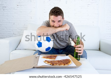 young man alone holding ball and beer bottle in stress watching football game on television sitting at home living room sofa couch with pizza box enjoying the match excited biting his arm nervous - stock photo