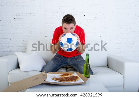 young man alone holding ball and kissing it in stress wearing team jersey watching football game on television at home living room sofa couch excited and anxious eating pizza drinking beer - stock photo