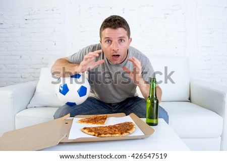 young man alone holding ball in stress watching football game on television sitting at home living room sofa couch with pizza box and beer bottle enjoying the match looking excited and shocked - stock photo