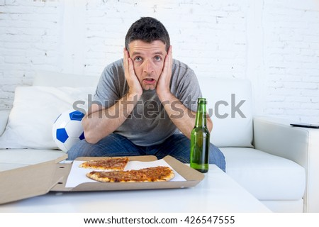 young man alone holding ball in stress watching football game on television sitting at home living room sofa couch with pizza box and beer bottle enjoying the match looking nervous and excited - stock photo