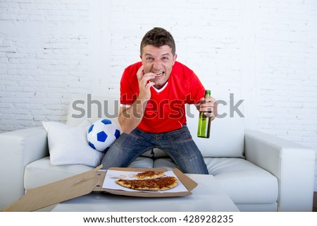 young man alone holding beer bottle eating pizza in stress wearing team jersey watching football game on television at home living room sofa couch excited in disbelief face expression - stock photo