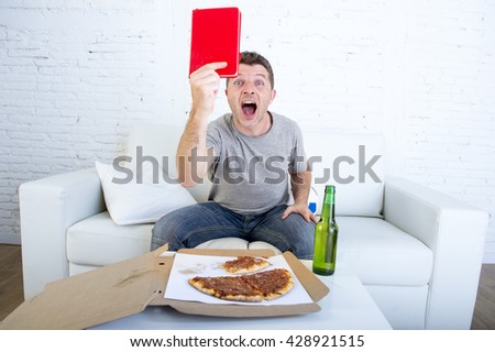 young man alone holding notepad showing it as referee red card in angry face expression in stress watching football game on television at home couch with pizza box and beer bottle  screaming excited  - stock photo