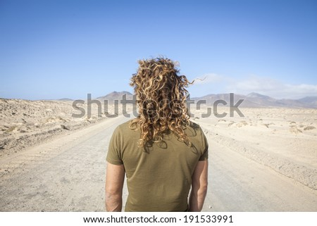 young man alone in a desert road - stock photo
