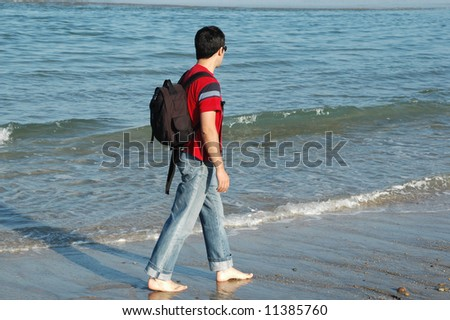 young man alone it walks for the sand of the beach...