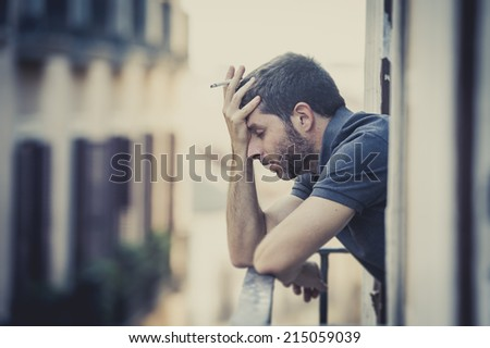 young man alone outside at house balcony terrace smoking depressed, destroyed, wasted and sad suffering emotional crisis and depression on urban background horizontal format - stock photo