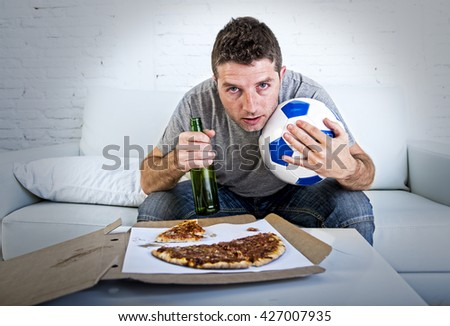 young man alone with red eyes holding ball and beer bottle in stress watching football game on television at home living room sofa couch with pizza excited  in crazy anxious face expression - stock photo