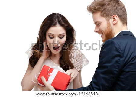 Young man amazes his pretty girlfriend with present wrapped in red paper, isolated on white - stock photo