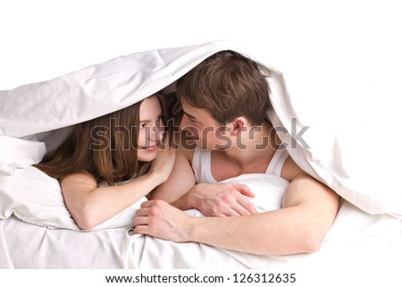 young man and beautiful girl in a bed under blanket on white background - stock photo