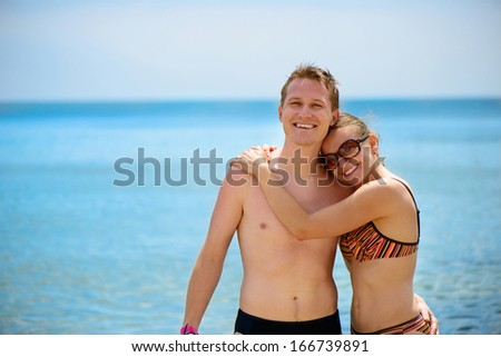 Young man and beautiful girl in sunglasses smiling at ocean beach