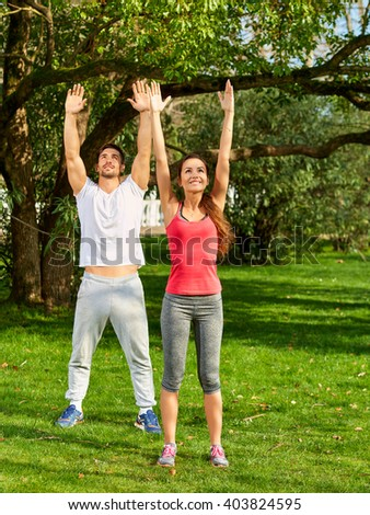 Young man and beautiful woman doing stretching exercises outdoors in the park. - stock photo