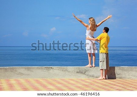 young man and beautiful woman on quay, woman lifted hands upwards - stock photo