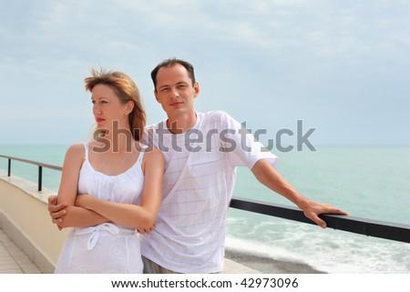 young man and beautiful woman on veranda near seacoast - stock photo