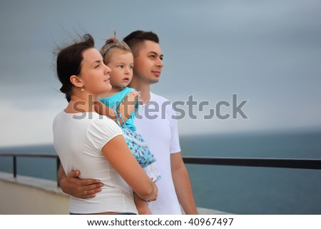 young man and beautiful woman protects little girl from wind on seacoast