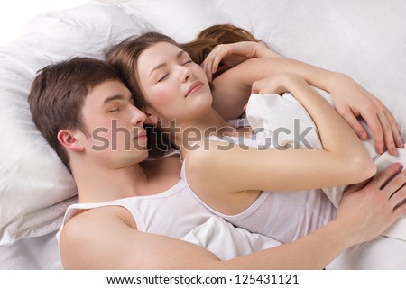 Young man and beautiful woman sleeping in a white bedding - stock photo